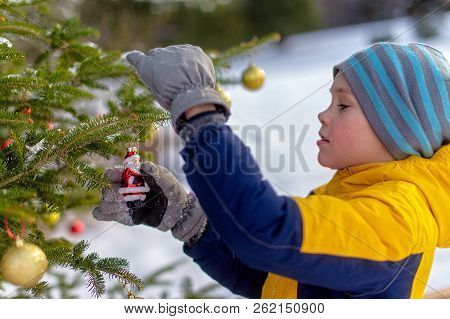 Boy Hanging Christmas Decorations On A Christmas Tree Outside. Child Holding A Santa Claus Holiday O