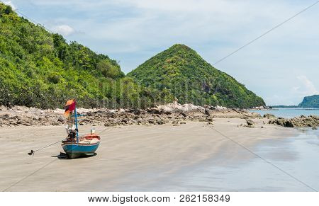 Blue Fishing Boat On Beach And Green Hill And Sea And Reef Or Rock. Fisherman Boat Or Fishing Boat F