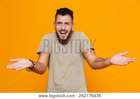 Portrait of a confused young casual man standing isolated over orange background, shrugging shoulders