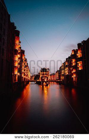 Hamburg, Germany. View Of Wandrahmsfleet During Sunset With Illuminated Buildings. Warehouse Landmar