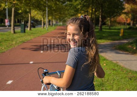 Happy Child Rides A Bike On Bike Path. Cyclist Child Or Teenager Girl Enjoys Good Weather And Cyclin