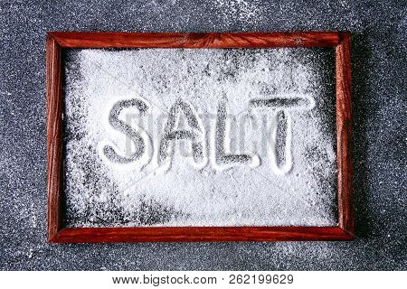The Word Salt Is Written On Small Crystals Of Salt Scattered On A Black Table. Background For Advert