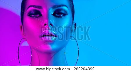 High Fashion model metallic silver lips and face woman in colorful bright neon uv blue and purple lights, posing in studio, beautiful girl, glowing make-up, colorful make up. Glitter Vivid neon makeup
