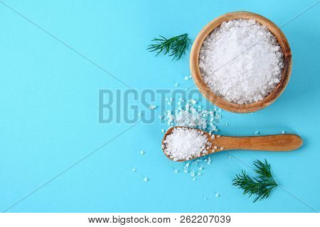 Crystals Of Large Sea Salt In A Wooden Bowl And Spoon And Dill On A Blue Table. Background For Adver