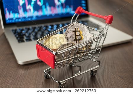 Shopping Trolley Full Of Bitcoin. Bitcoin Currency With Laptop Showing Stock Market Rates. Bitcoin P