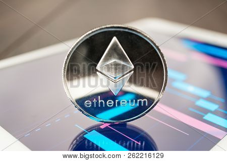 Close-up Photo Of Ether Cryptocurrency. Ether Physical Coin On The Tablet Computer. Tablet Showing E
