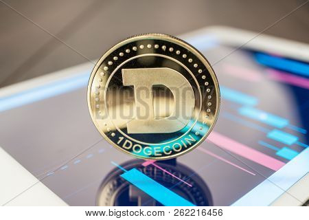 Close-up Photo Of Dogecoin Cryptocurrency. Dogecoin Physical Coin On The Tablet Computer. Tablet Sho