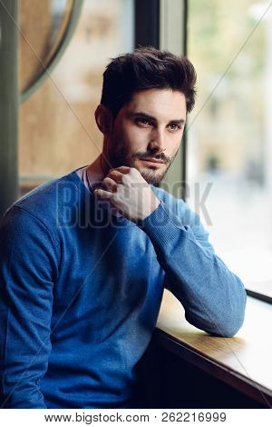 Thoughtful Man With Blue Sweater With Lost Look Near A Window In A Modern Pub. Bearded Guy With Mode