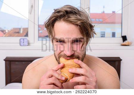 Guy Holds Croissant Bedroom Hotel Room Window Background. Enjoy Every Bite. Man Eats Croissant He Li
