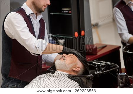Unrecognizable Barber Wiping Head Of Client With Towel In Black Wash Basin. Male Hairdresser Styling