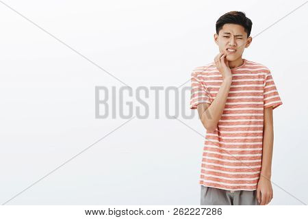 Uneasy Attractive Young Asian Male Student Having Tooth Decay Touching Cheek Reacting On Pain, Havin