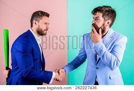 Businessman Hides Bat Behind Back While Shaking Hands. Hidden Threat Concept. Business Partners Comp