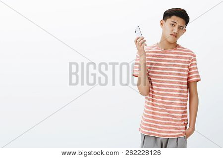Bossy Serious-looking Cool Young Teenage Asian Guy In Striped T-shirt Taking Away Smartphone As Bein