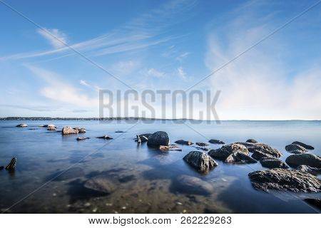 Rocks By The Ocean In The Calm Water Under A Beautiful Blue Sky