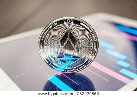 Close-up Photo Of Eos Cryptocurrency. Eos Physical Coin On The Tablet Computer. Tablet Showing Eos S