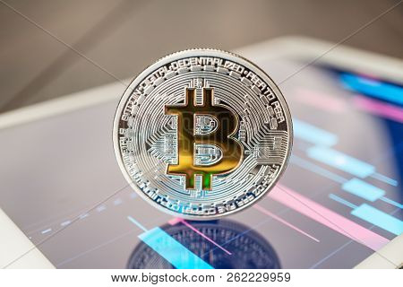 Close-up Photo Of Bitcoin Cryptocurrency. Bitcoin Physical Coin On The Tablet Computer. Tablet Showi