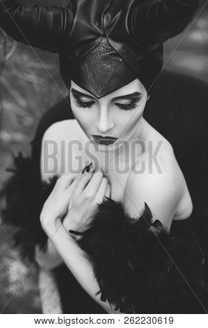Stylish And Fashionable Brunette Model Girl In The Image Of Maleficent Posing Among Mystic Forest -