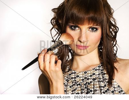 a beautiful brunette woman putting on make-up on white background