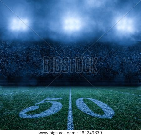 American Football Stadium at night 50 yard line. Stadium lights on a misty clouded night. Nobody in the photo, background only