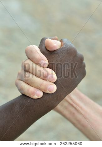 Multi-ethnic Hands In Handshake Close-up On Abstract Background
