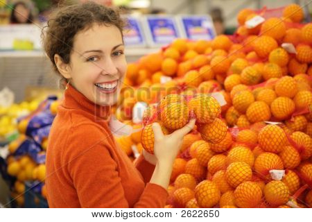 Young Woman With Oranges In Store