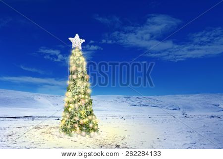 Conceptual image of decorated Christmas tree with colorful lights and ornaments  on snow covered landscape