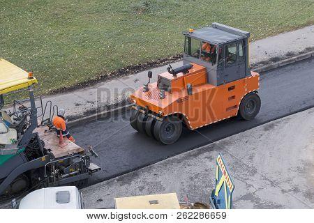 Road Renewal Process. Roller Compactor Machine Presses New Asphalt. A Worker And Asphalt Paver Are N