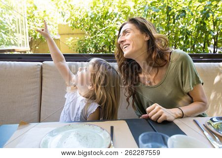 Girl Pointing With Finger Up Next To Smiling Woman In Restaurant