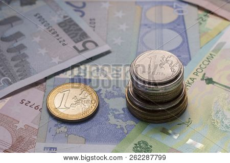 1 Euro (EUR) coin and stack of Ruble or rouble (RUR) coins. Exchange rate. Banknote background poster