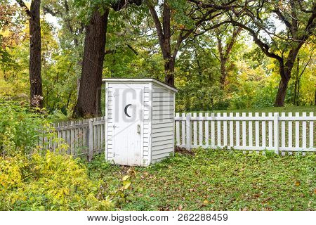 Vintage White Outhouse And White Picket Fence In Rural United States.