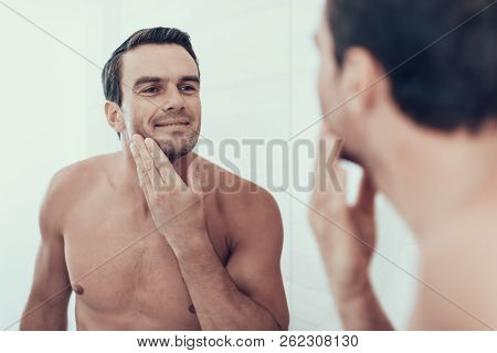 Happy Man In Bathroom Check Beard After Shaving. Portrait Of Smiling Cheerful Caucasian Brown Haired