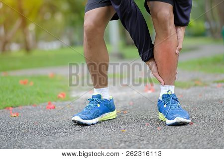 Young Fitness Man Holding His Sports Leg Injury, Muscle Painful During Training. Asian Runner Having