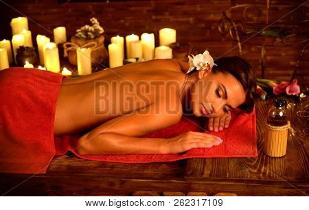 Ayurveda massage of woman in spa salon. Girl on candles background in massage spa salon. Thai massage and relaxes mind.