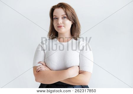 Portrait Of Confident Smiling Businesswoman. Pretty Young Female Entrepreneur Standing With Her Arms