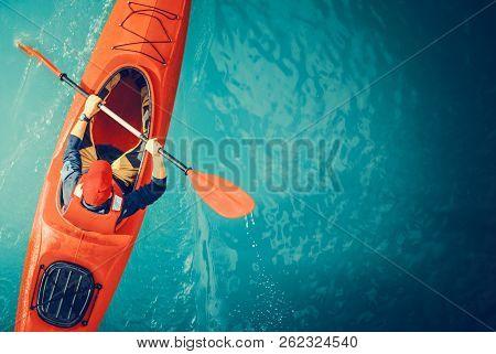 Kayaker Lake Tour Aerial Photo. Red Kayak And Caucasian Paddling Sportsman In His 30s.