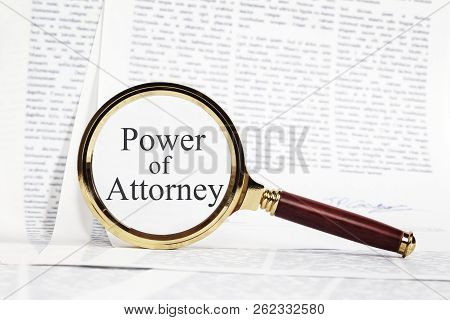 Power Of Attorney Concept - Paperwork Representing A Power Of Attorney, With A Magnifying Glass Over