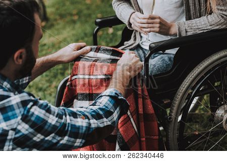 Girl On Wheelchairs With Man On Picnic In Park. Disabled Young Woman. Woman On Wheelchair. Relaxing