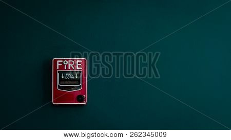 Fire Alarm On Dark Green Concrete Wall. Warning And Security System. Emergency Equipment For Safety