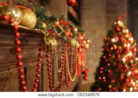 Christmas interior with decoorated wooden fake fireplace and bright christmas tree in studio, focus on fireplace part