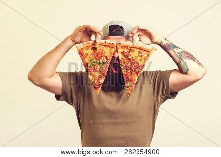 Happy Hungry Man Eating Pizza. Bearded Man Holds Two Pieces Of Pizza In His Hands. Excited Guy In Ca