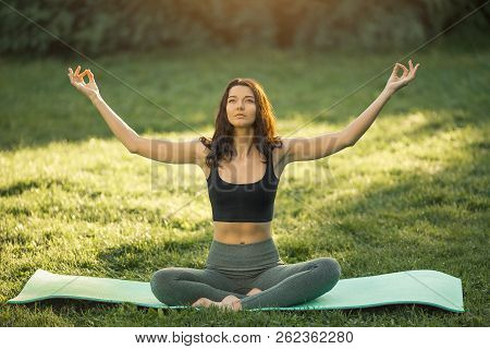 Young Girl Doing Yoga In The Park. Woman Practicing Yoga Performing Lotus Position Outdoors With Clo