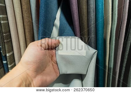 A Young Man Examines The Label On The Fabric.