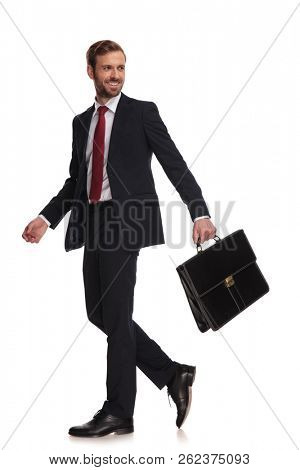 side view of happy businessman holding briefcase walking on white background and looking to side, full length picture