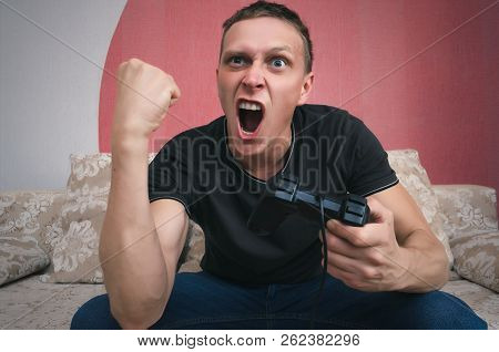 Aggressive gamer man with gamepad in the hand is playing in video game and is shaking his fist. Win a game concept. poster