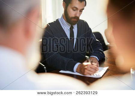 Young bearded applicant writing down answers in questionnaire list while sitting in front of his employers during interview