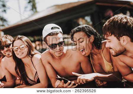 Young Smiling Friends Using Smartphone At Poolside. Group Of Young Happy People Talking And Using Ce