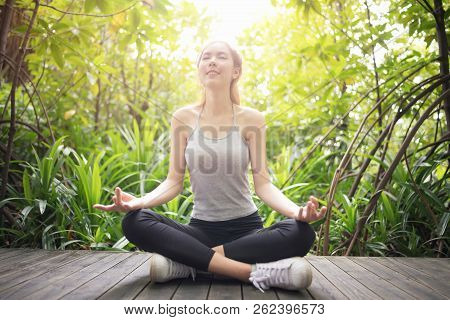 Asian Woman Relaxing Yoga Pose At The Park.