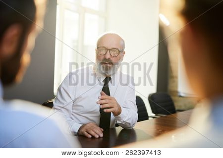 Elegant senior applicant telling about himself during conversation with employers at interview