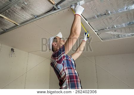 Young Handsome Man In Casual Clothing Takes Measurement Of Drywall Suspended Ceiling Connected To Me