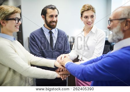 Cheerful young colleagues looking at their aged director while making pile of hands altogether